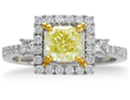 This gorgeous engagement ring should be yours!  This ring boasts a .91 carat princess-cut yellow diamond.  The stone is surrounded with a halo of round brilliant diamonds followed by two beautiful princess cut diamonds.  This ring is set in 18 karat white gold with yellow gold prongs.  Total carat weight 1 1/2 carat, G-H color and SI1 clarity.  It is available in ring sizes 5.5-8.5.